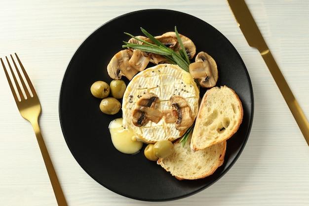Concept de plats savoureux avec camembert grillé sur fond de bois blanc.