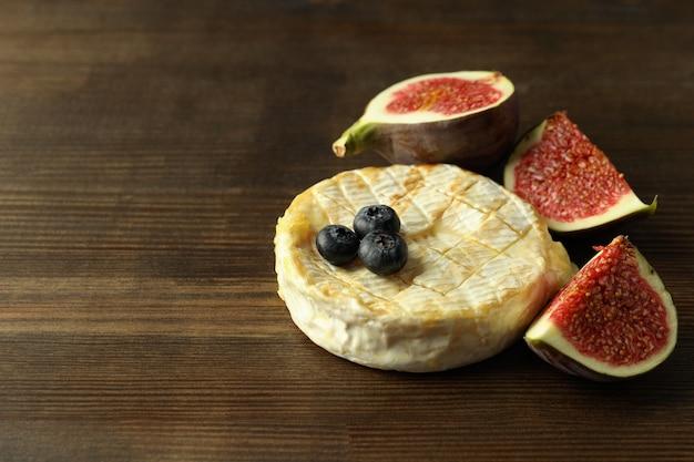 Concept de plats savoureux avec camembert grillé sur fond de bois.