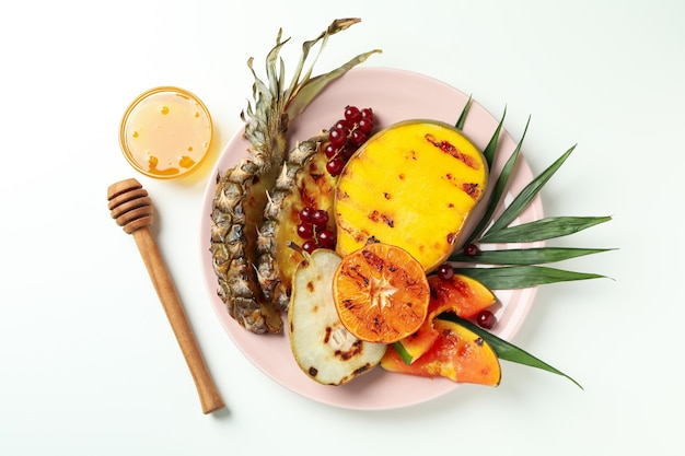 Concept de plats savoureux avec des fruits grillés sur fond blanc.