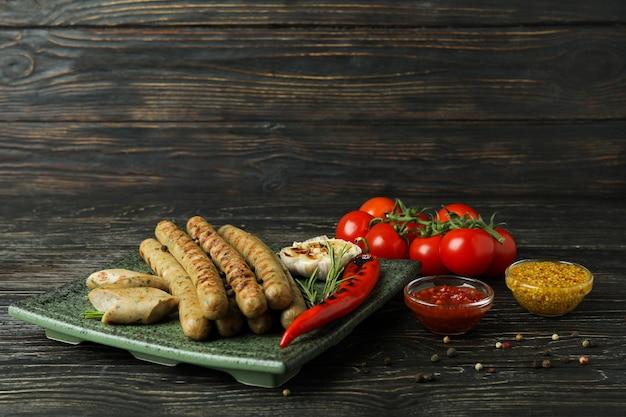 Concept de plats savoureux avec des saucisses grillées sur table en bois