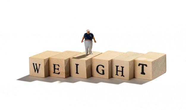 Concept de poids avec une figure de gros garçon miniature