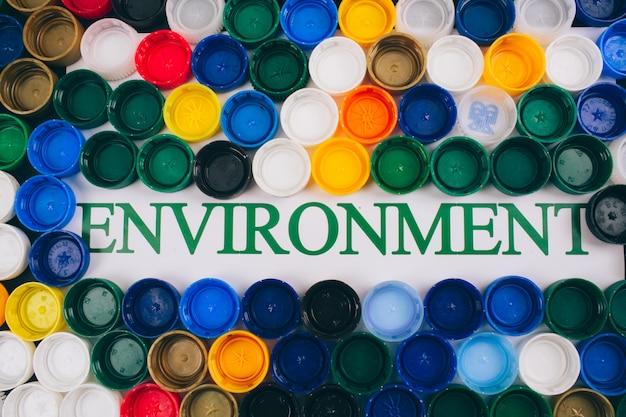 Concept de pollution en plastique. soyez sans plastique. environnement word au centre de l'arrière-plan coloré de différents couvercles en plastique, vue de dessus. plastiques à usage unique, directive européenne de l'ue pour aider l'environnement