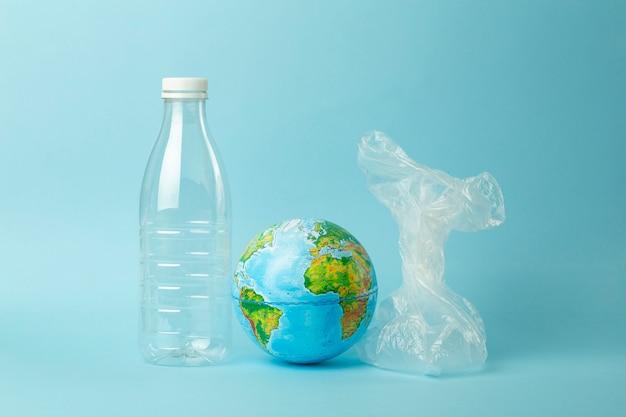 Concept de pollution de sac en plastique. globe terrestre dans un sac en plastique sur un fond coloré. plastiques et pollution des océans, nature