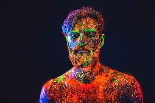 Concept. portrait d'un homme barbu. l'homme est peint en poudre ultraviolette.