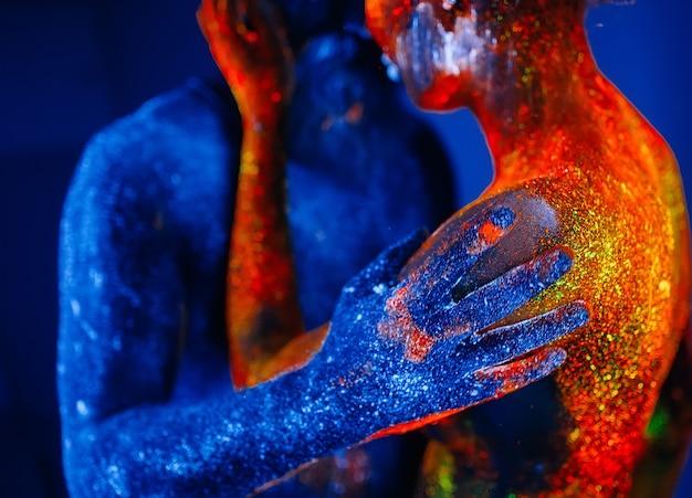 Concept. portrait d'un homme et d'une femme barbus peints dans une poudre ultraviolette.
