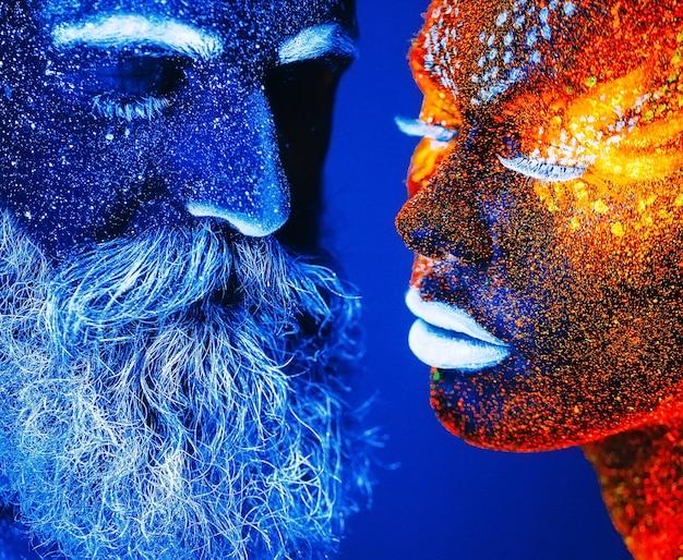 Concept. portrait d'un homme et d'une femme barbus peints en poudre ultraviolette.