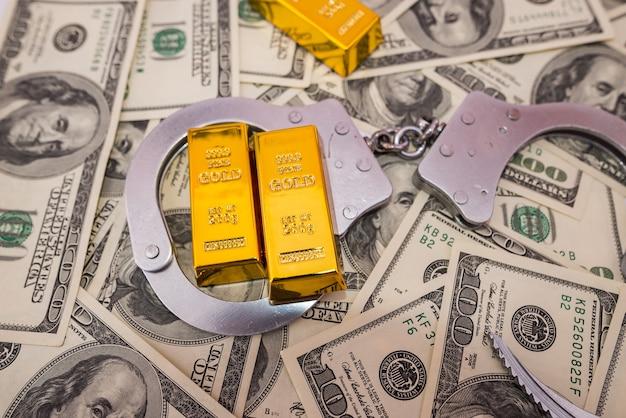 Concept de pot-de-vin, lingots d'or et menottes sur les billets d'un dollar