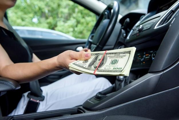 Concept de pot-de-vin. mains féminines donnant un paquet de dollars à l'intérieur de la voiture close up