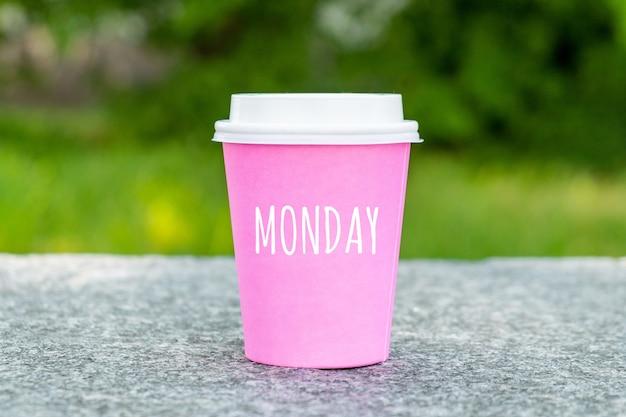 Concept pour le début du lundi sur une tasse de café jetable.