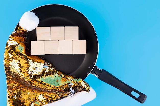 Concept pour écrire du texte sur sept cubes en bois qui se trouvent dans une poêle à frire et un chapeau de père noël. espace de copie.