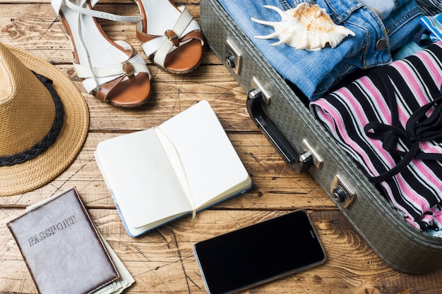 Concept de préparatifs de voyage avec valise, vêtements et accessoires sur une vieille table en bois. vue de dessus espace de copie