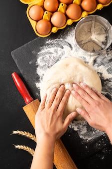 Concept de préparation des aliments sur la balle dans la tête pétrir la pâte pour la boulangerie, la pizza ou les pâtes sur fond noir avec espace de copie