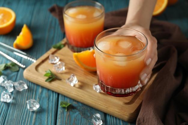 Concept de préparation du cocktail tequila sunrise sur table en bois