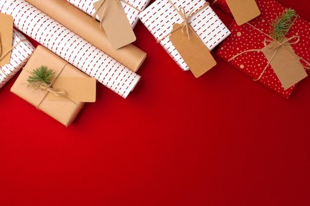 Concept de préparations de noël avec papier d'emballage, coffrets cadeaux sur rouge
