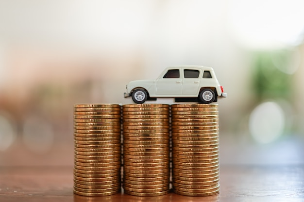 Concept de prêt de finance d'entreprise automobile. gros plan du jouet de voiture miniature blanche sur une pile de pièces avec copie espace.