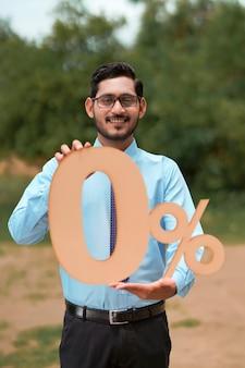 Concept de prêt de véhicule : jeune banquier ou financier indien montrant le symbole du signe zéro pour cent.