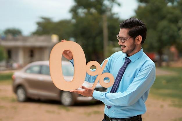 Concept de prêt de véhicule : jeune banquier ou financier indien montrant un symbole de signe zéro pour cent sur un nouveau véhicule