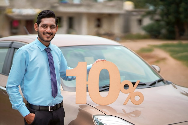 Concept de prêt de véhicule : jeune banquier indien montrant le symbole de dix pour cent sur la nouvelle voiture