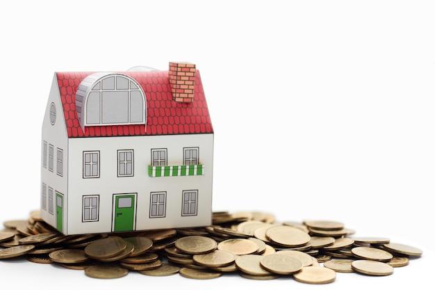 Concept de prêts immobiliers, maison miniature sur un tas de pièces de monnaie.