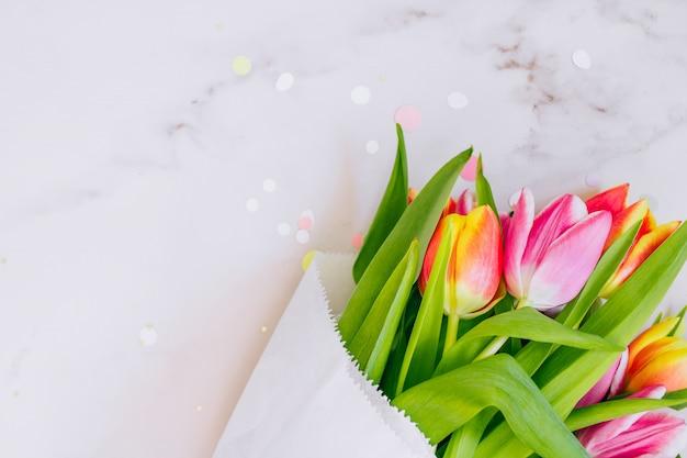 Concept de printemps. décorations étoiles dorées, confettis vibrants et tulipes roses et rouges sur fond de marbre. espace de copie, pose à plat.