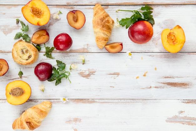 Concept de printemps ou d'été avec pêches, prunes, raisins et pâtisseries