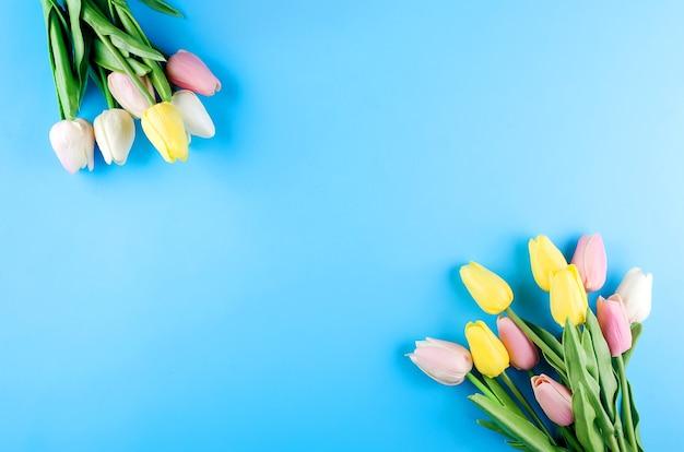 Concept de printemps ou de vacances, un bouquet de tulipes sur fond bleu