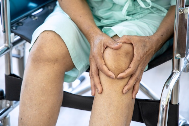 Concept de problème de santé; vieille femme souffrant de douleurs au genou à l'hôpital.