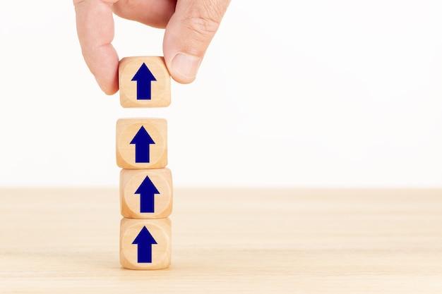 Concept de processus de croissance d'entreprise. main tenant un bloc en bois avec l'icône de la flèche.