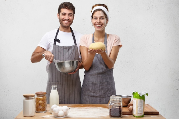 Concept de produits, nourriture, cuisine et cuisine. portrait de l'heureux jeune couple européen positif la cuisson du pain fait maison