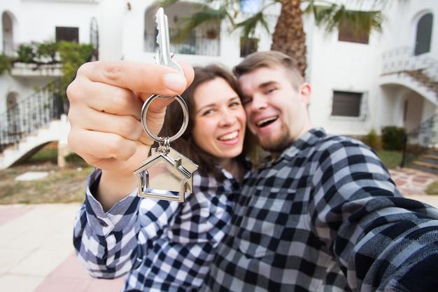Concept de propriété, immobilier et appartement - heureux jeune couple drôle montrant les clés de leur nouveau