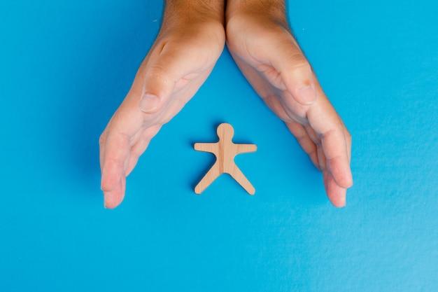 Concept de protection sociale sur table bleue à plat. mains en prenant soin de la figure humaine en bois.