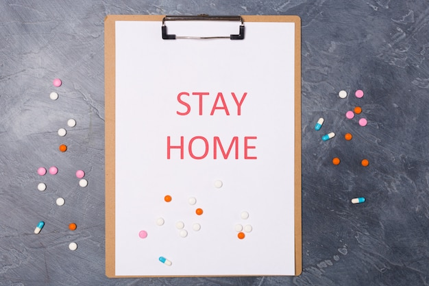 Concept de protection. vue de dessus des mots rester à la maison avec des médicaments. concept minimal. restez en sécurité, concept