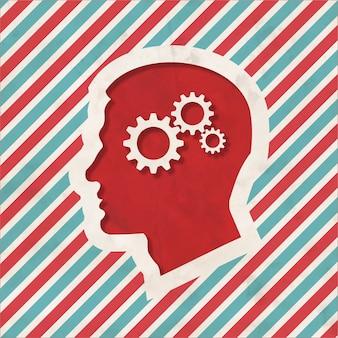Concept psychologique - profil de tête avec mécanisme d'engrenage à crémaillère - sur fond rayé rouge et bleu. concept vintage au design plat.