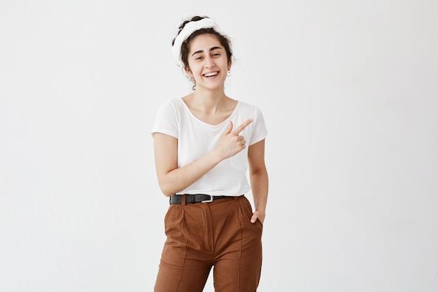 Concept publicitaire. prise de vue en intérieur d'une jeune femme sympathique positive avec des cheveux ondulés sombres en chignon pointant vers l'espace de copie sur le mur blanc pour votre texte ou contenu promotionnel