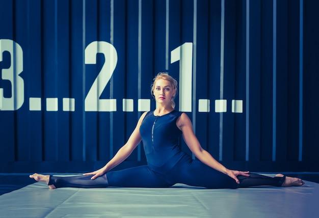Concept : puissance, force, mode de vie sain, sport. entraîneur crossfit puissant et séduisant d'une femme musclée faisant des exercices d'étirement ou des étirements de ficelle pendant l'entraînement au gymnase