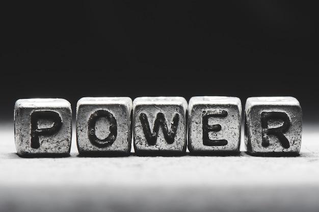 Concept de puissance. inscription 3d sur des cubes métalliques sur fond noir gris isolé