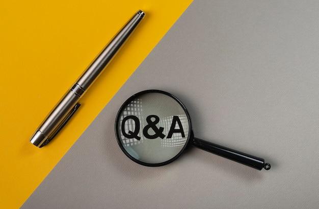 Concept q ou qa à travers une loupe sur une table de couleur jaune et grise.