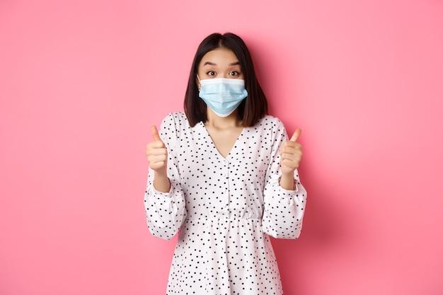 Le concept de quarantaine et de mode de vie de covid a excité une femme asiatique en masque facial montrant le pouce levé faisant l'éloge...