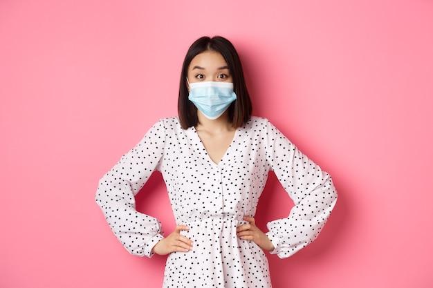 Concept de quarantaine et de mode de vie covid jolie femme coréenne en robe et masque facial utilisant des mesures préventives ...