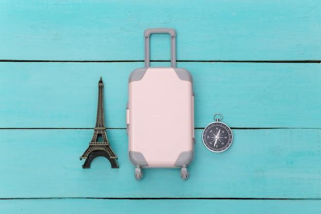 Concept de rabotage de vacances et de voyage à plat. mini valise de voyage en plastique, figurine de la tour eiffel, boussole sur fond de bois bleu. vue de dessus
