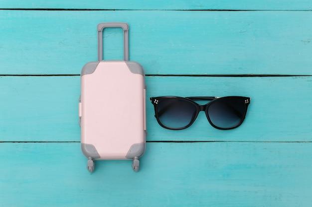 Concept de rabotage de vacances et de voyage à plat. mini valise de voyage en plastique, lunettes de soleil sur fond de bois bleu. vue de dessus
