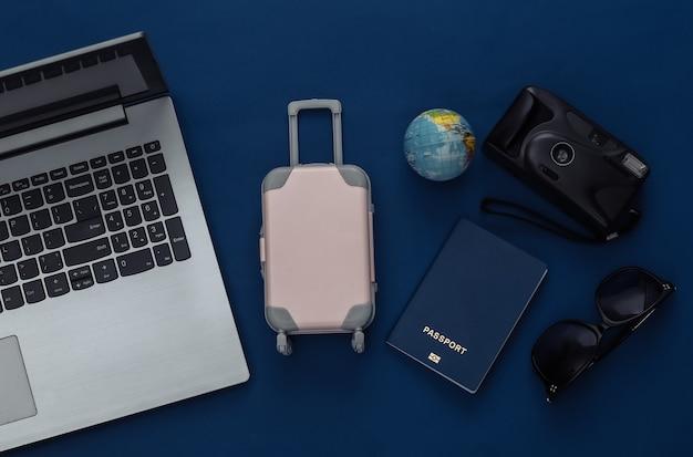 Concept de rabotage de vacances et de voyage à plat. ordinateur portable et accessoires de voyage sur fond bleu classique. vue de dessus