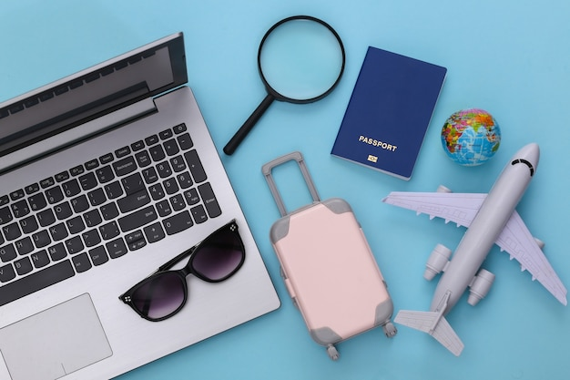 Concept de rabotage de vacances et de voyage à plat. ordinateur portable et accessoires de voyage sur fond bleu. vue de dessus