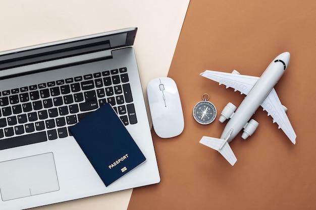 Concept de rabotage de vacances et de voyage à plat. ordinateur portable et accessoires de voyage sur fond marron beige. vue de dessus