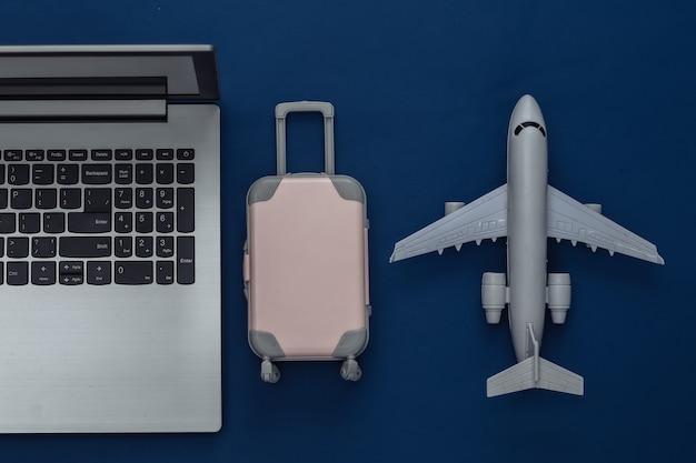 Concept de rabotage de vacances et de voyage à plat. ordinateur portable et mini valise de voyage en plastique, avion sur fond bleu classique. vue de dessus