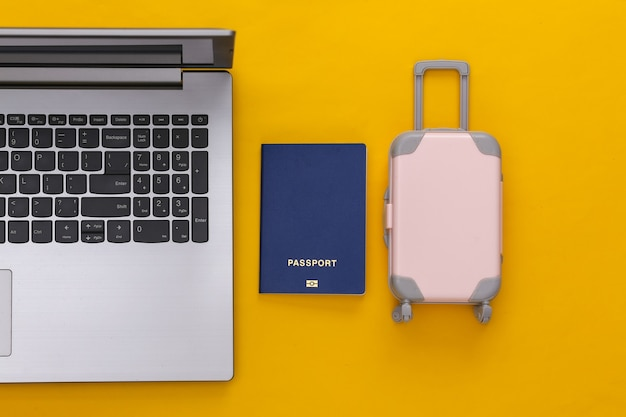 Concept de rabotage de vacances et de voyage à plat. ordinateur portable et mini valise de voyage en plastique, passeport sur fond jaune. vue de dessus