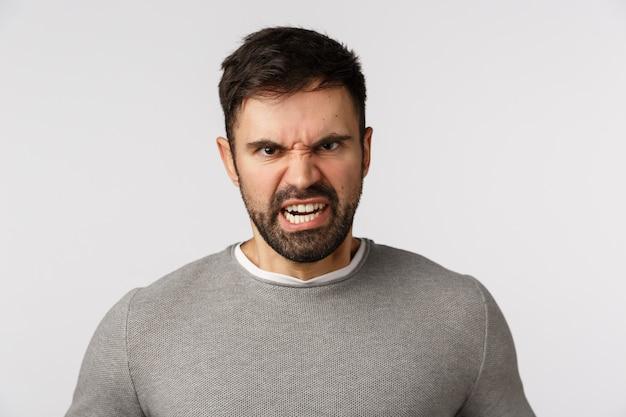 Concept de rage, d'agression et de haine. outraged and furious barbu adult man froncer les sourcils, grimacer le regard dérangé et dégoûté, exprimer le mépris ou le dédain, maudissant quelqu'un qui veut se battre