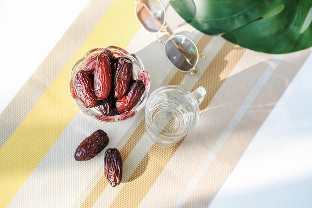 Concept ramadan et quelques palmiers dattiers avec un verre d'eau sur un présentoir à couleurs chaudes