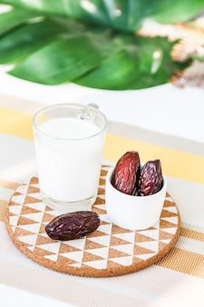 Concept ramadan et quelques palmiers dattiers avec un verre de lait sur un présentoir à couleurs chaudes
