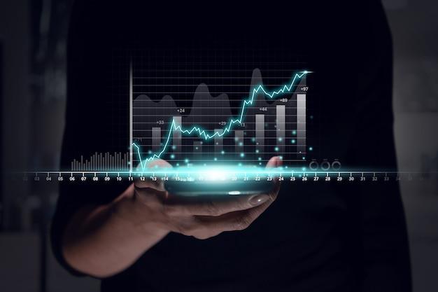 Concept de rapport d'activité de profit avec un design futuriste et des graphiques sur la main avec un smartphone.
